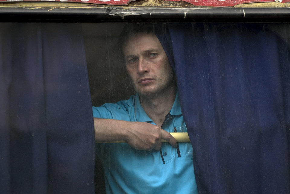 Photo - A man looks out of the back window of a bus in Donetsk, Ukraine, Monday May 19, 2014. Ukraine will hold presidential elections on May 25. (AP Photo/Vadim Ghirda)
