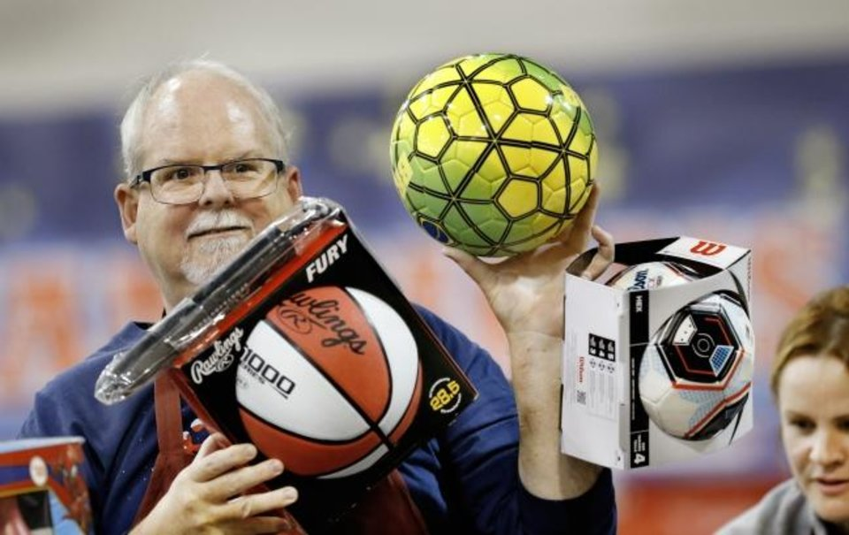 Photo -  Gary Davis, of Edmond, holds different types of sports balls for children and guests to see before making their toy selection at last year's Red Andrews Dinner. [The Oklahoman Archives]