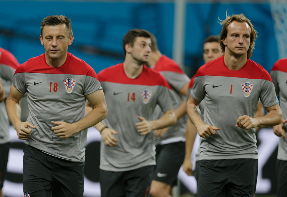 Photo - Croatia's Ivica Olic,left ,Marcelo Brozovic, center, and Ivan Rakitic warmup during an official training session the day before the group A World Cup soccer match between Cameroon and Croatia, at the Arena da Amazonia in Manaus, Brazil, Tuesday, June 17, 2014.  (AP Photo/Fernando Llano)