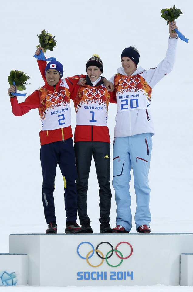 Photo - Germany's gold medal winner Eric Frenzel  is flanked by Japan's silver medal winner Akito Watabe, left, and Norway's bronze medal winner Magnus Krog  during the flower ceremony for the Nordic combined at the 2014 Winter Olympics, Wednesday, Feb. 12, 2014, in Krasnaya Polyana, Russia. (AP Photo/Matthias Schrader)