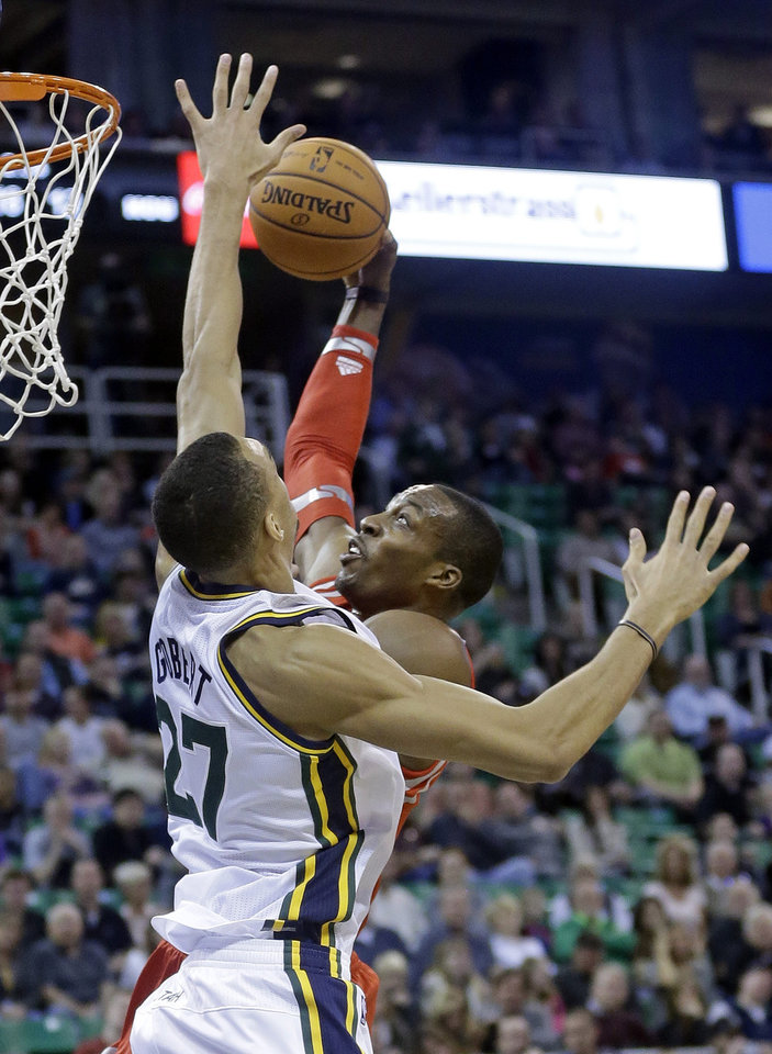 Photo - Houston Rockets' Dwight Howard, right, goes to the basket as Utah Jazz's Rudy Gobert (27), of France, defends in the first quarter during an NBA basketball game Saturday, Nov. 2, 2013, in Salt Lake City.  (AP Photo/Rick Bowmer)