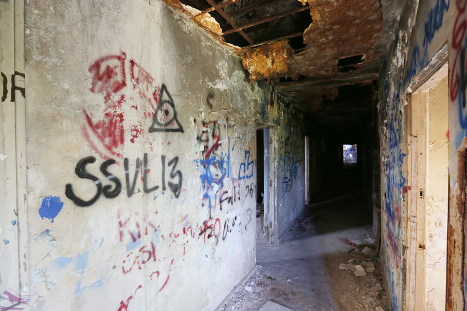Photo -   Above:  Graffiti is spread across walls and ceilings that are falling down at St. Vincent's Home in northeast Oklahoma City. [Photos by Paul Hellstern, The Oklahoman]