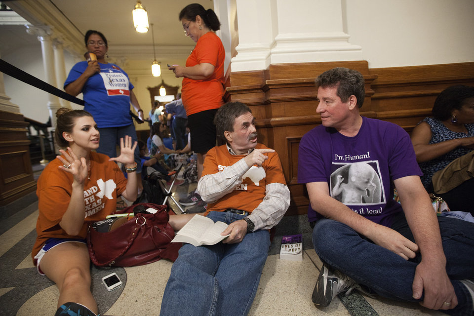 Pro-choice supporters Jessica Nenow, left, and Art Stretton, center, debate abortion rights with Brian McAuliffe, who is against abortions, while waiting in line to enter the Senate gallery at the Texas State Capitol in Austin, Texas, Friday, July 12, 2013. Texas Senate leader, Lt. Gov. David Dewhurst has scheduled a vote for Friday on the same restrictions on when, where and how women may obtain abortions in Texas that failed to become law after a Democratic filibuster and raucous protesters were able to run out the clock on an earlier special session. (AP Photo/Tamir Kalifa)