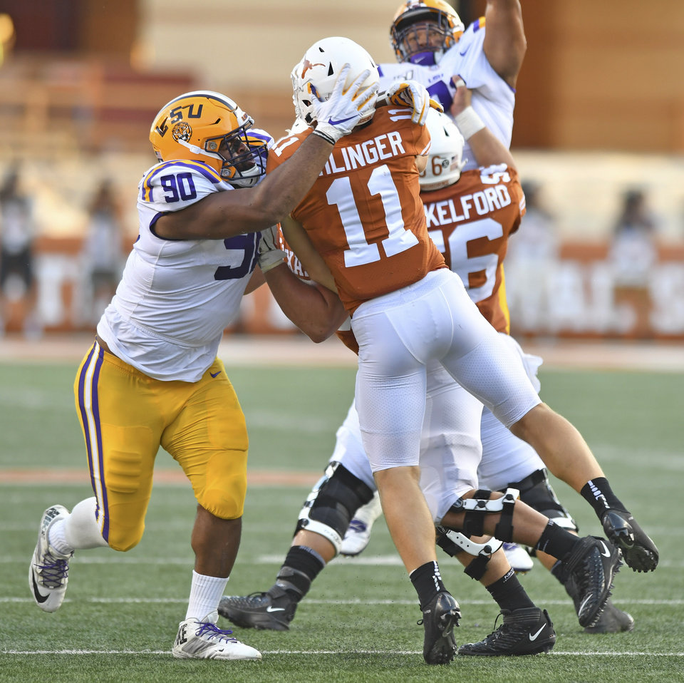 Photo - LSU defensive lineman Rashard Lawrence (90) hits Texas quarterback Sam Ehlinger (11) during an NCAA college football game Saturday, Sept. 7, 2019, in Austin, Texas. (Hilary Scheinuk/The Advocate via AP)