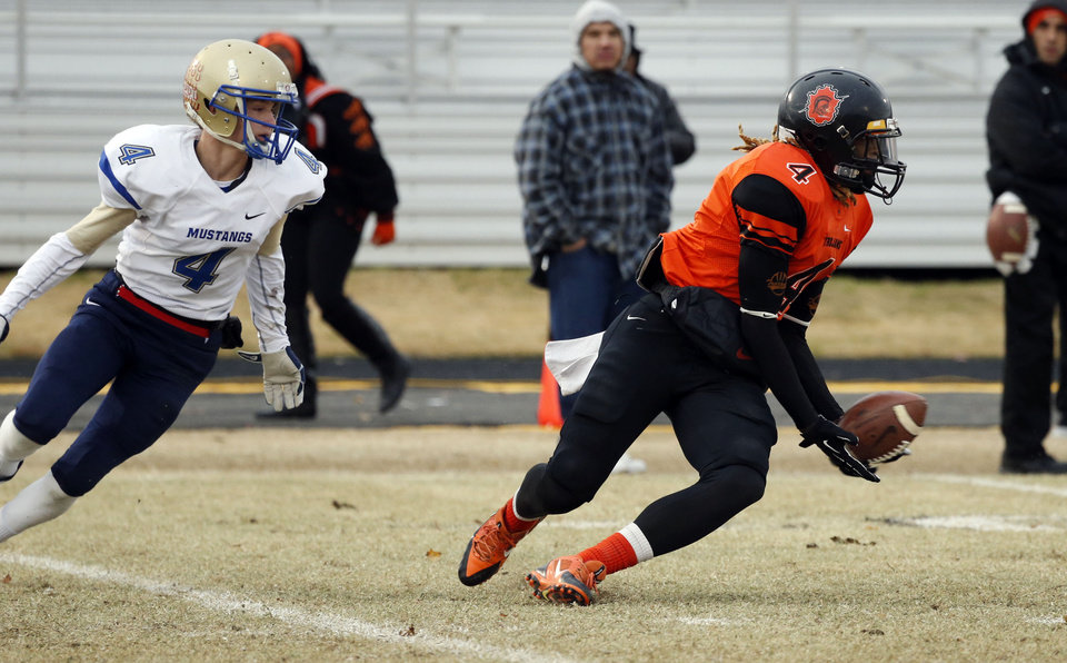 Photo - Douglass' Dameko Doddles catches a pass in the second half as the Trojans come from behind to defeat Oologah in high school football playoff action on Saturday, Nov. 23, 2013, in Oklahoma City, Okla. Oologah defender Drake Barnes is at left.  Photo by Steve Sisney, The Oklahoman