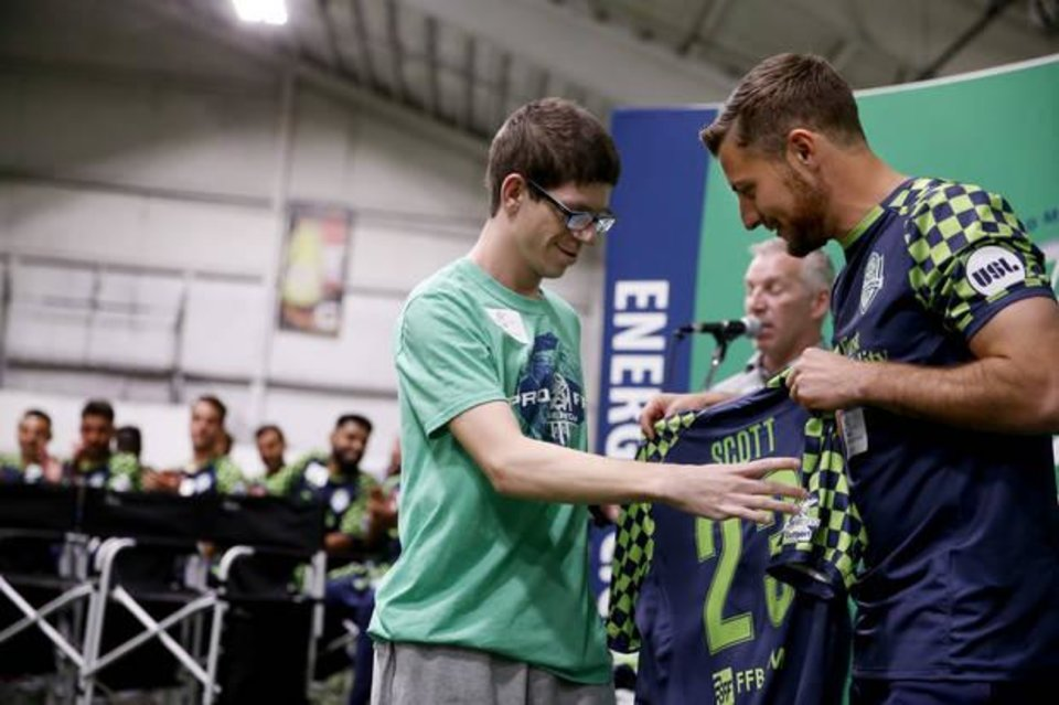 Photo -  Energy FC player Shawn McLaws presents Sidekick friend William Scott with a jersey during an event last month in Oklahoma City. [PHOTO BY BRYAN TERRY, THE OKLAHOMAN]