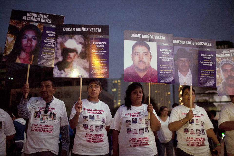 """FILE - In this May 9, 2012 file photo, people hold photographs of their relatives who went missing during a protest that is part of the campaign """"March of National Dignity. Mothers searching their sons and justice"""" held at the Revolution Monument in Mexico City.  A new report by a civic participation group has put a number for the first time on the human toll of all the violence: 20,851 people disappeared over the past six years, although not every case on the list may be related to the drug war. With at least another 70,000 people having died in drug violence, the numbers point to a brutal episode in Mexico that ranks among Latin America's deadliest in decades.  (AP Photo/Alexandre Meneghini, File)"""