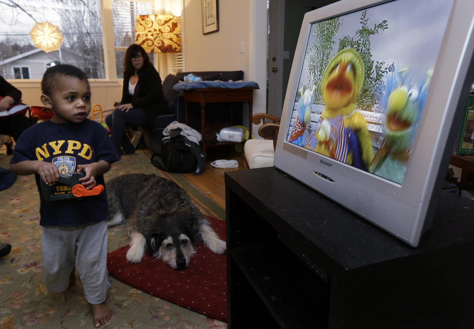 EMBARGOED UNTIL MIDNIGHT EASTERN TIME SUNDAY, FEB. 17 - Nancy Jensen, second from left, looks on as her son Joe, 2, is given a special treat of a little TV time Tuesday, Feb. 12, 2013 at their home in Seattle. Nancy was a participant in a new University of Washington study on the effects of television viewing on kids that will be published Monday, Feb. 18, 2013. (AP Photo/Ted S. Warren)
