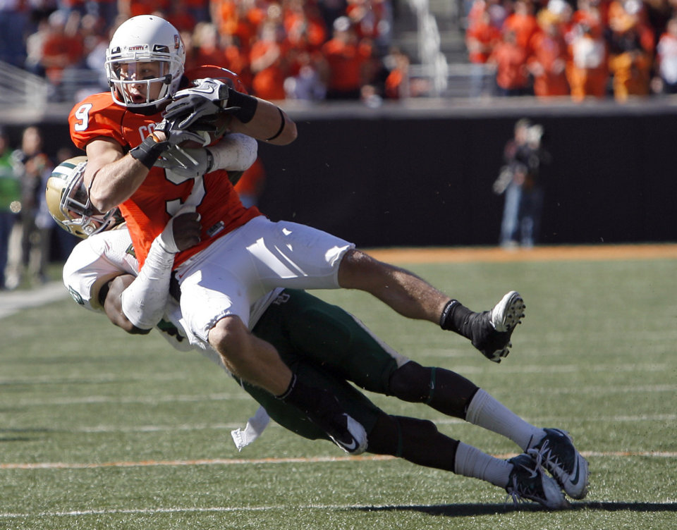 Photo - OSU's Bo Bowling is brought down by Baylor's Chris Francis during the college football game between the Oklahoma State University Cowboys (OSU) and the Baylor University Bears at Boone Pickens Stadium in Stillwater, Okla., Saturday, Nov. 6, 2010. Photo by Sarah Phipps, The Oklahoman