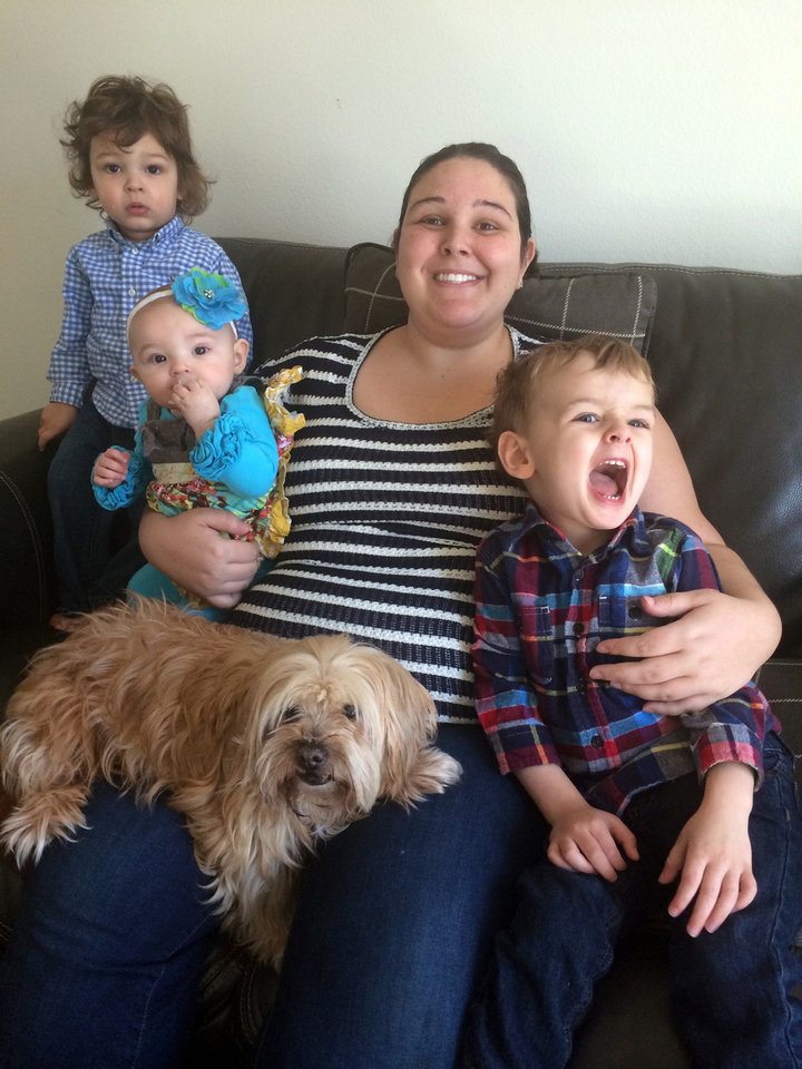 Photo - In this March 24, 2014 photo provided by Sharon Norris, Britany Spangler, of Grand Rapids, Mich., center poses with her children, from left, son Noah, 1; daughter Scarlett, 6 months; and son Lucas, 3, and their adopted 12-year-old Lhasa Apso named Molly. Spangler adopted Molly after the dog was featured on the Susie's Seniors Facebook page. Molly may not have more than six months to live, but Norris, who is expecting, says she will take her for whatever time she can have her. (AP Photo/Sharon Norris)
