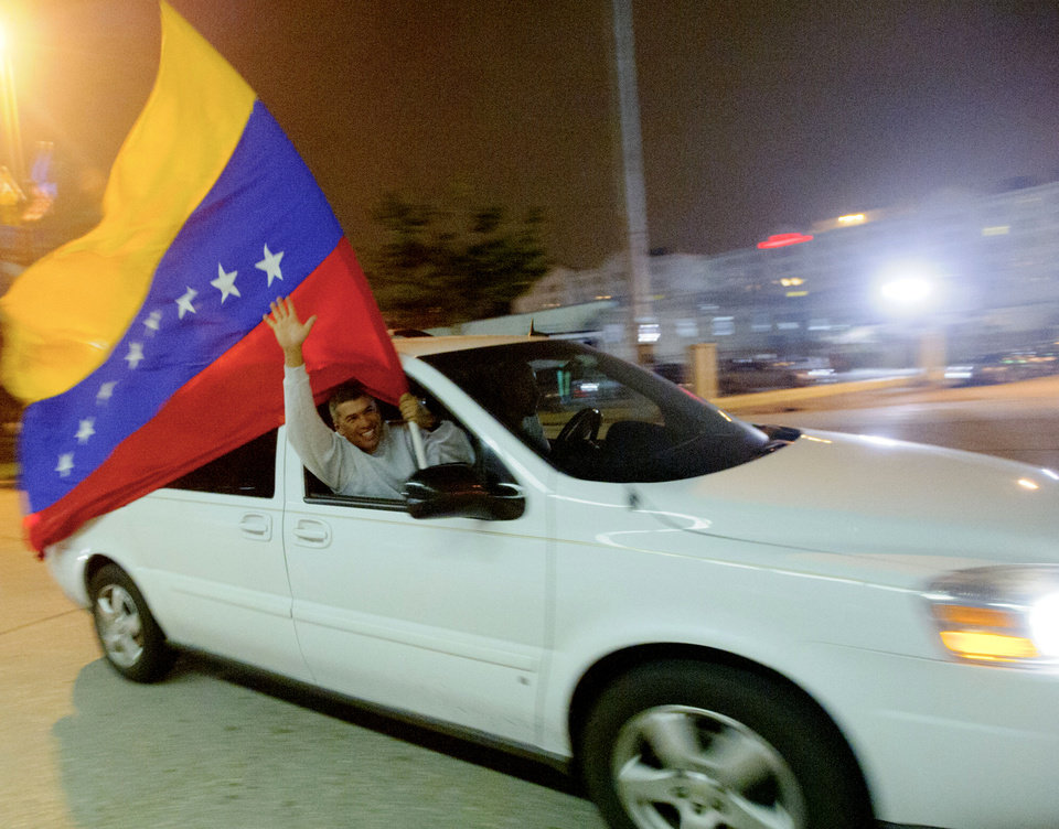 Photo -   Freddy Moros holds a Venezuela flag as he waves to people waiting in line to vote at the New Orleans Ernest Morial Convention Center, in New Orleans, Sunday, Oct. 7, 2012. Hundreds of Venezuelans living in the U.S. streamed into New Orleans on Sunday to cast ballots in the presidential election in their homeland, many of them determined to end the 13-year reign of Hugo Chavez. With the country's consulate in Miami closed, thousands of Venezuelans traveled by bus, car and plane to cast their votes at the consulate in New Orleans. (AP Photo/Matthew Hinton)