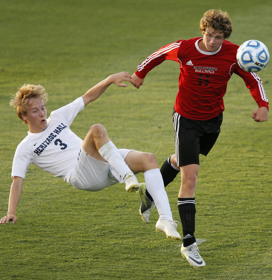 Photo - Heritage Hall's Garret McLaughlin, left, and Skiatook's Bryce Shook fight for the ball during the Class 5A boys soccer championship between Heritage Hall and Skiatook in Norman, Okla., Friday, May 16, 2014. Photo by Bryan Terry, The Oklahoman