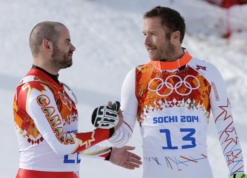 Photo - Men's super-G joint bronze medal winners Canada's Jan Hudec and United States' Bode Miller shake hands on the podium during a flower ceremony at the Sochi 2014 Winter Olympics, Sunday, Feb. 16, 2014, in Krasnaya Polyana, Russia. (AP Photo/Christophe Ena)