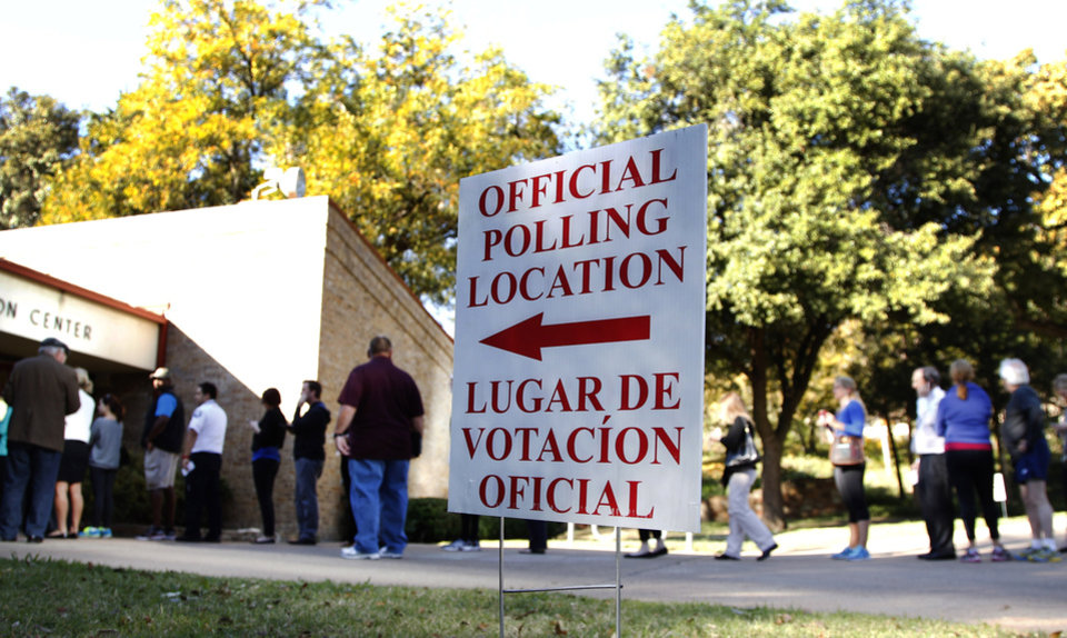 Photo -   A sign guides voters to a polling location as they line up to cast their votes Tuesday, Nov. 6, 2012, in Dallas. After a grinding presidential campaign, Americans head into polling places across the country. (AP Photo/Tony Gutierrez)