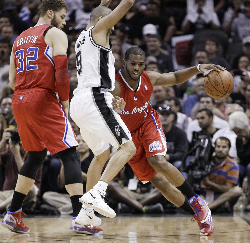 Photo -   Los Angeles Clippers' Chris Paul, right, drives against San Antonio Spurs' Tony Parker, center, of France, as Clippers' Blake Griffin watches during the first quarter of Game 2 of an NBA basketball Western Conference semifinal playoff series, Thursday, May 17, 2012, in San Antonio. (AP Photo/Eric Gay)