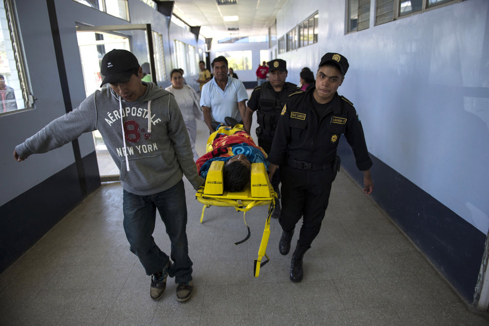 Photo - Luciano Perez is carried on a stretcher by police and volunteers inside a hospital after he was injured during earthquake in San Marcos, Guatemala, Monday, July 7, 2014. A magnitude-6.9 earthquake on the Pacific Coast jolted a wide area of southern Mexico and Central America Monday. (AP Photo/Oliver de Ros)