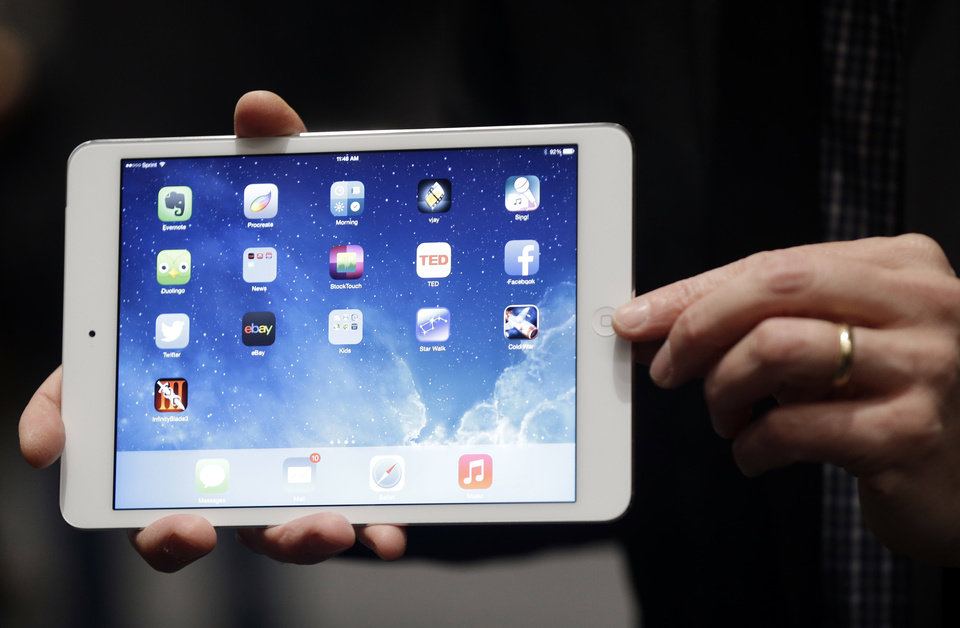 "An Apple employee demonstrates the new iPad Mini on Tuesday in San Francisco. Apple unveiled a new, thinner, lighter tablet called the ""iPad Air"" and the iPad Mini with Retina Display, along with a slew of new Macs. AP Photos"