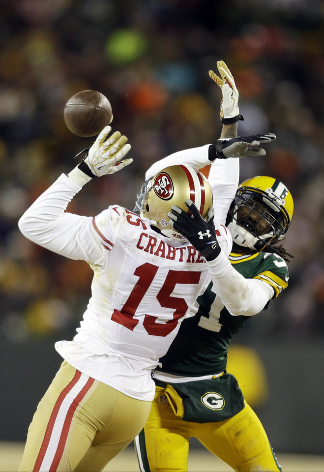 Photo - Green Bay Packers cornerback Davon House (31) breaks up a pass intended for San Francisco 49ers wide receiver Michael Crabtree (15) during the second half of an NFL wild-card playoff football game, Sunday, Jan. 5, 2014, in Green Bay, Wis. The 49ers won 23-20. (AP Photo/Jeffrey Phelps)