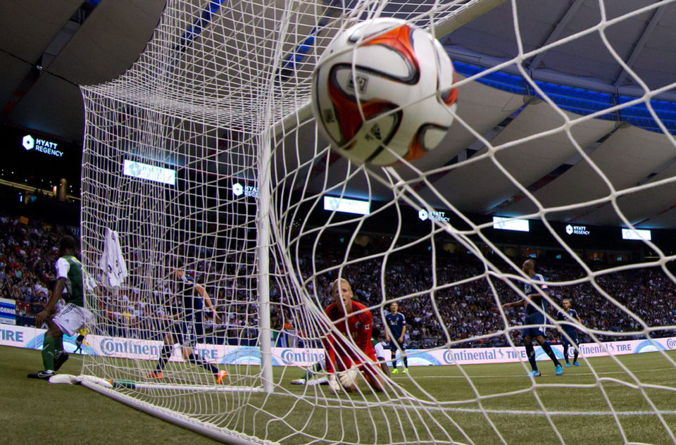 Photo - Vancouver Whitecaps goalkeeper David Ousted, of Denmark, looks back into the net after allowing a goal to Portland Timbers' Alvas Powell during the second half of an MLS soccer game in Vancouver, British Columbia, on Saturday, Aug. 30, 2014. (AP Photo/The Canadian Press, Darryl Dyck)