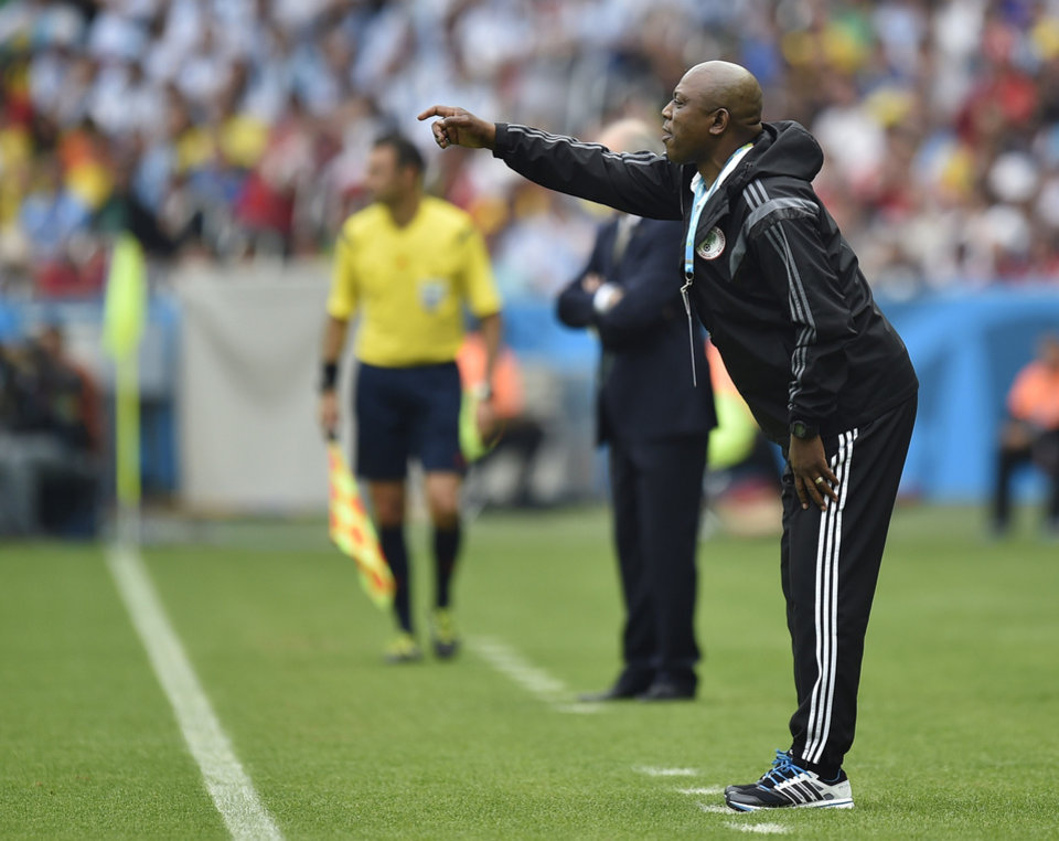 Photo - Nigeria's coach Stephen Keshi gives instructions to his players during the group F World Cup soccer match against Argentina at the Estadio Beira-Rio in Porto Alegre, Brazil, Wednesday, June 25, 2014. (AP Photo/Martin Meissner)