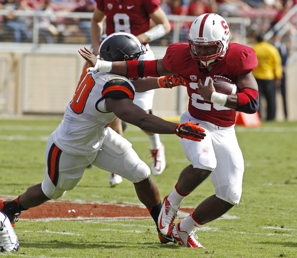 Photo - Stanford's Barry Sanders, right, runs with the ball as Oregon State's Michael Doctor chases during the first half of an NCAA college football game, Saturday, Oct. 25, 2014, in Stanford, Calif. (AP Photo/George Nikitin)