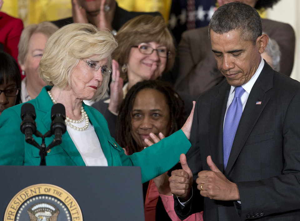 Photo - President Barack Obama gives two thumbs as Women's rights activist Lilly Ledbetter, left, acknowledges him in the East Room of the White House in Washington, Tuesday, April 8, 2014, during an event marking Equal Pay Day, and where the president will announce and sign new executive actions to strengthen enforcement of equal pay laws for women. The president and his Democratic allies in Congress are making a concerted election-year push to draw attention to women's wages, linking Obama executive actions with pending Senate legislation aimed at closing a compensation gendergap that favors men. (AP Photo/Carolyn Kaster)