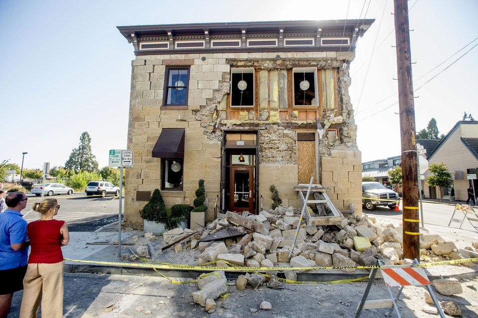 Photo - Pedestrians stop to examine a crumbling facade at the Vintner's Collective tasting room in Napa, Calif., following an earthquake Sunday, Aug. 24, 2014. Officials in the city of Napa say 15 to 16 buildings are no longer inhabitable after Sunday's magnitude-6.0 earthquake, and there is only limited access to numerous other structures. (AP Photo/Noah Berger)