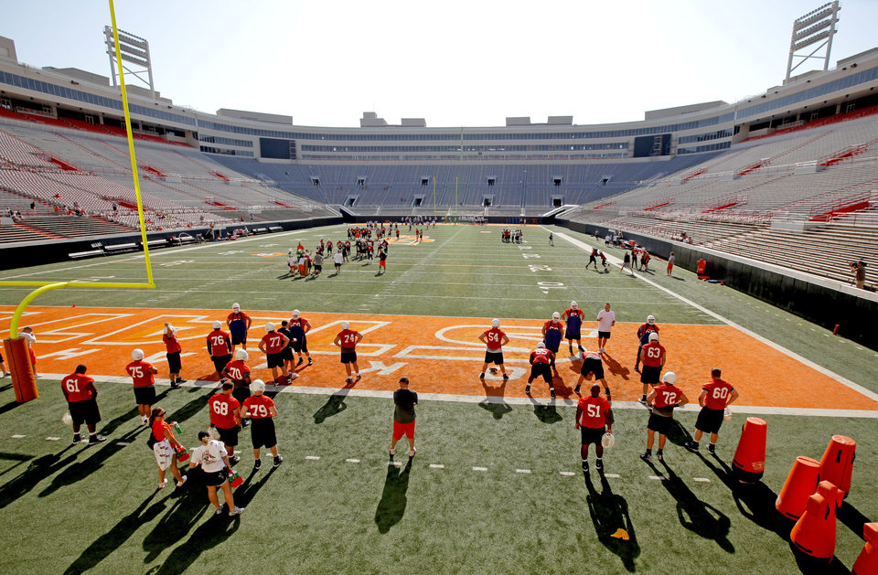Photo - Oklahoma State players take to the field for the first day of practice Wednesday at Boone Pickens Stadium in Stillwater. (Photo by Bryan Terry, The Oklahoman)