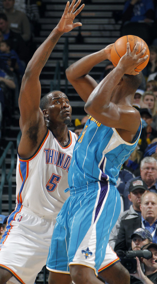 Photo - Oklahoma City Thunder center Kendrick Perkins (5) defends on New Orleans Hornets center Emeka Okafor (50) during the NBA basketball game between the Oklahoma City Thunder and the New Orleans Hornets at the Chesapeake Energy Arena on Wednesday, Jan. 25, 2012, in Oklahoma City, Okla. Photo by Chris Landsberger, The Oklahoman