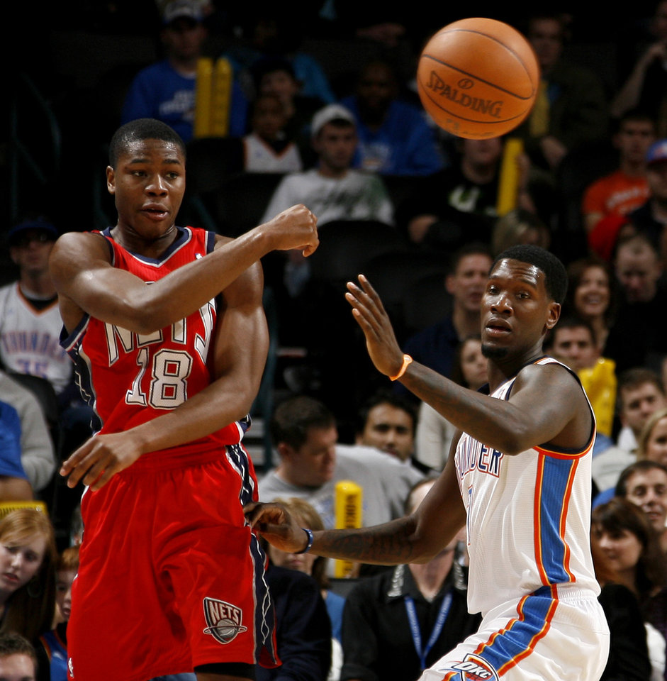 Photo - New Jersey's Ben Uzoh passes the ball around Oklahoma City's Royal Ivey during the NBA basketball game between the Oklahoma City Thunder and the New Jersey Nets at the Oklahoma City Arena, Wednesday, Dec. 29, 2010.  Photo by Bryan Terry, The Oklahoman