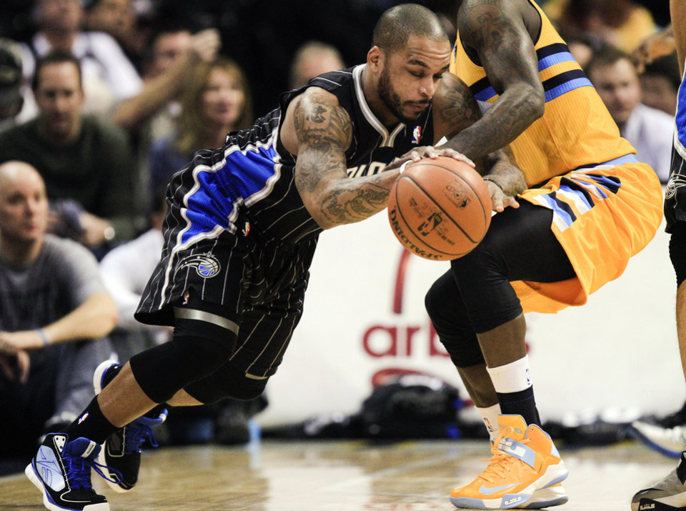 Photo - Orlando Magic's Jameer Nelson, left, drives past Denver Nuggets' Ty Lawson (3) during the first quarter of an NBA basketball game, Wednesday, Jan. 9, 2013, in Denver. (AP Photo/Barry Gutierrez)