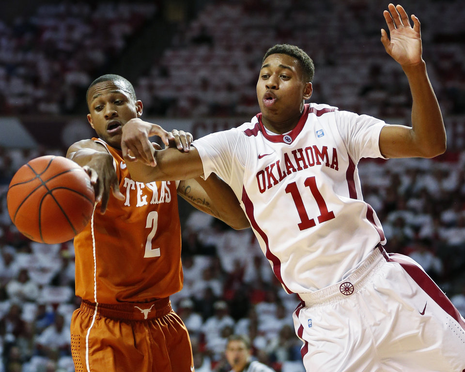 Photo - Texas' Demarcus Holland (2) knocks the ball away from Oklahoma's Isaiah Cousins (11) during an NCAA college basketball game in Norman, Okla., Monday, Jan. 21, 2013. (AP Photo/The Oklahoman, Nate Billings)