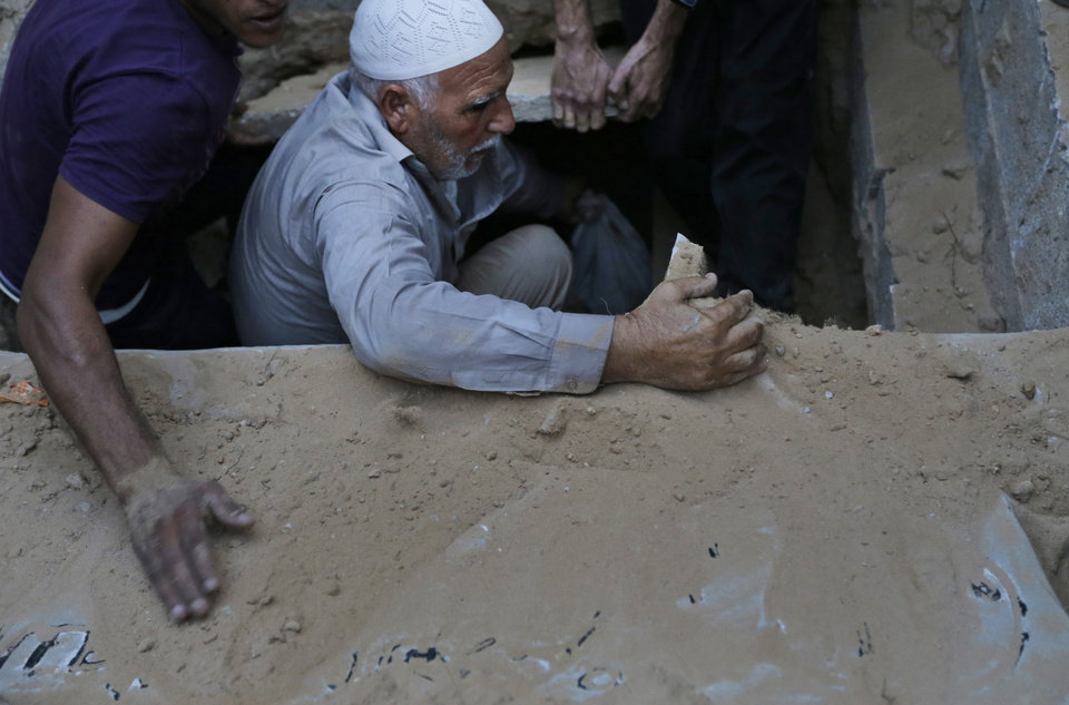 Photo - Palestinians throw soil into the grave of Muhammed Abu Shagfa, 7, killed in an explosion, during the funeral in Gaza City, in the northern Gaza Strip, Monday, July 28, 2014. An explosion killed 10 people, 9 of them children, at a park at Shati refugee camp, in northern Gaza Strip. Israeli and Palestinian authorities traded blame over the attack and fighting in the war raged on despite a major Muslim holiday. (AP Photo/Lefteris Pitarakis)