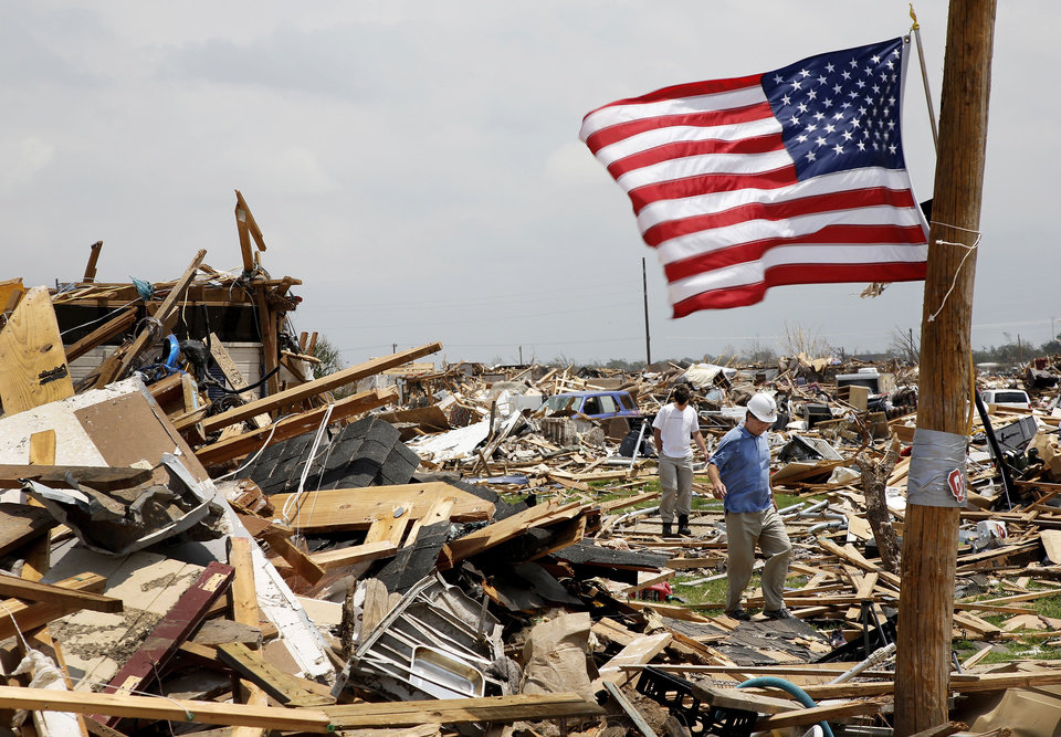 Photo - People walk through rubble in the Westmoor neighborhood near SW 147 and Harvey on Wednesday.  Jim Beckel - THE OKLAHOMAN