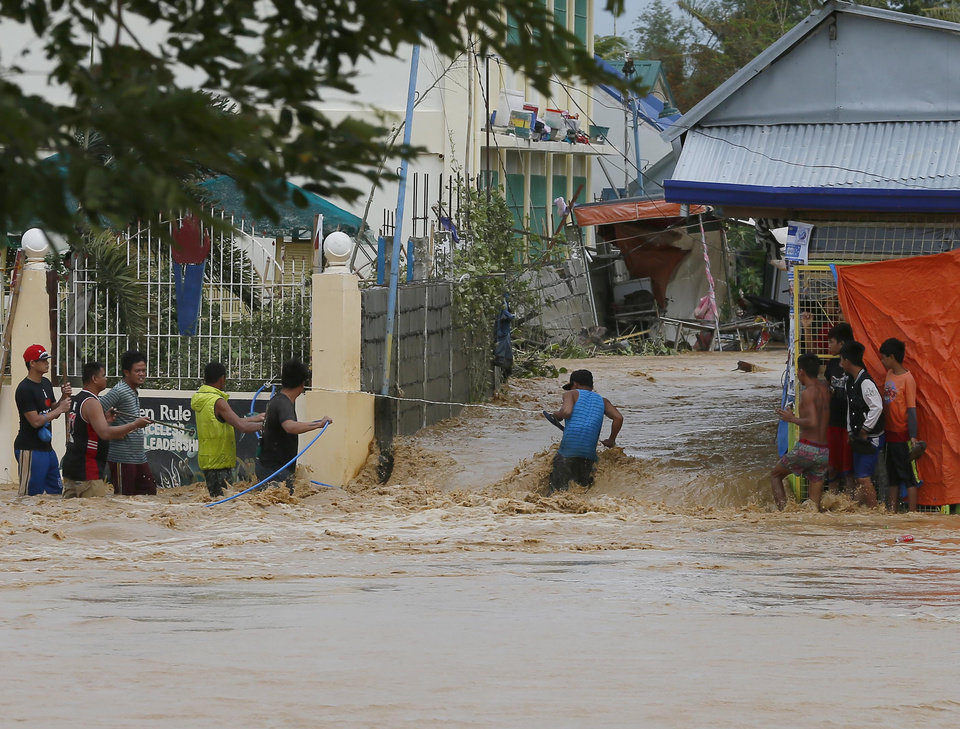 Photo - Residents use a rope to cross through raging floodwaters brought about by Typhoon Koppu at Zaragosa township Nueva Ecija province north of Manila, Philippines Monday, Oct. 19, 2015. Slow-moving Typhoon Koppu blew ashore with fierce wind in the northeastern Philippines early Sunday, toppling trees and knocking out power and communications and forcing the evacuation of thousands of villagers.(AP Photo/Bullit Marquez)