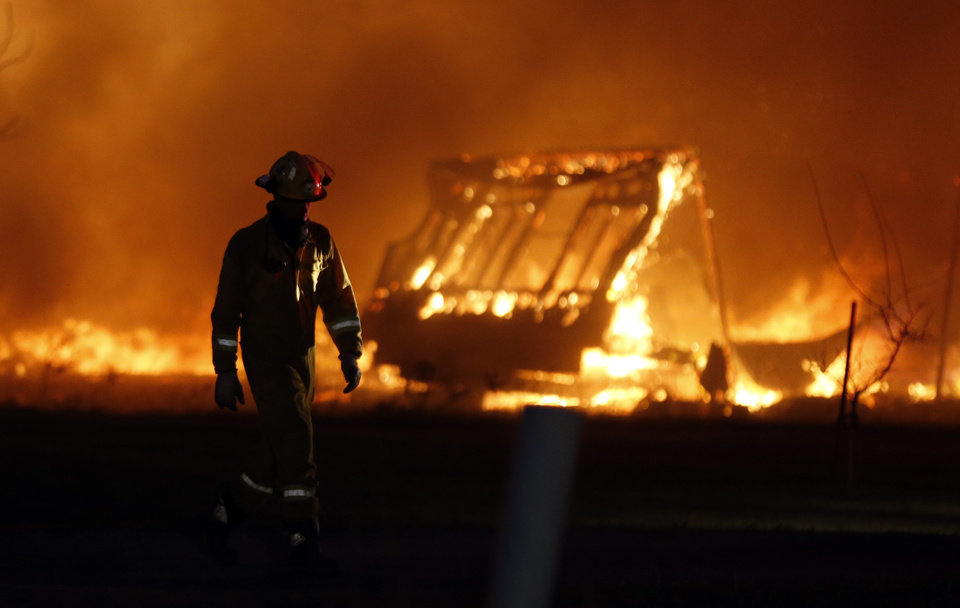 A firefighter walks past a burning mobile home at a mobile home park near Prairie Grove Rd. and Douglas during wildfires in south Logan County, Sunday, May 4, 2014. Photo by Nate Billings, The Oklahoman