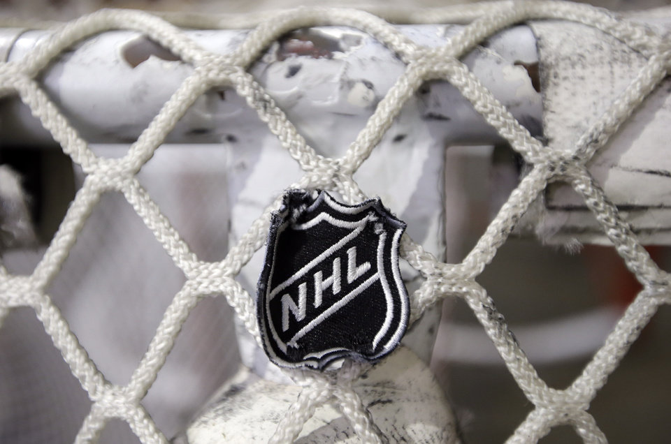 Photo -   The NHL logo is seen on a goal at a Nashville Predators practice rink on Monday, Sept. 17, 2012, in Nashville, Tenn. The NHL locked out its players at midnight Saturday, the fourth shutdown for the NHL since 1992. (AP Photo/Mark Humphrey)