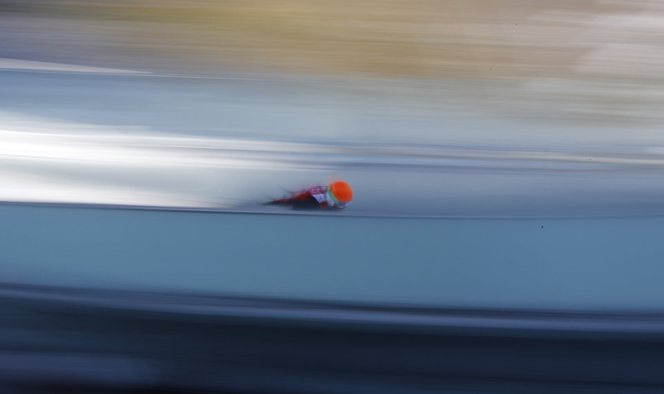 Photo - In this slow shutter speed photo an unidentified athlete starts an attempt during the men's normal hill ski jumping training at the 2014 Winter Olympics, Friday, Feb. 7, 2014, in Krasnaya Polyana, Russia. (AP Photo/Matthias Schrader)