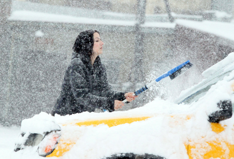Photo - This motorist fights a losing battle as heavy snow covers her vehicle as quickly as she clears it on 8th Street near Washington Tuesday March 5, 2013 in Michigan City, Ind. (AP Photo/The News Dispatch, Bob Wellinski)