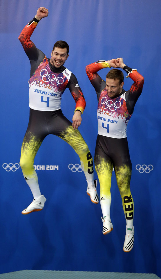 Photo - The doubles team of Tobias Wendl and Tobias Arlt from Germany jump onto the podium for the flower ceremony after they won the gold medal during the men's doubles luge at the 2014 Winter Olympics, Wednesday, Feb. 12, 2014, in Krasnaya Polyana, Russia. (AP Photo/Dita Alangkara)
