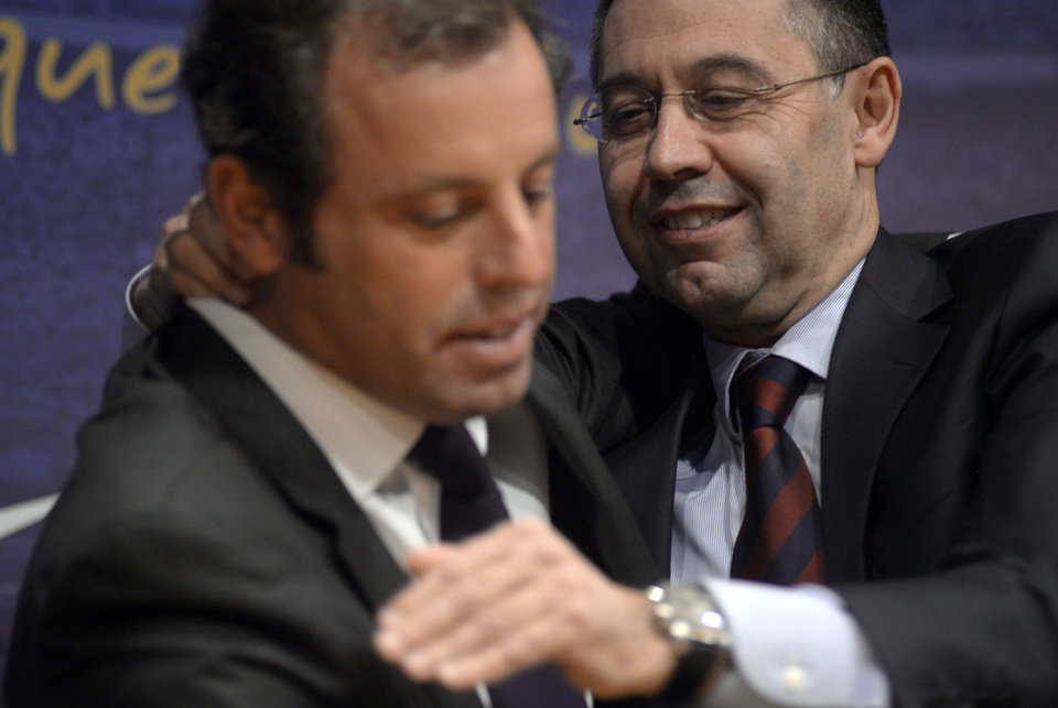 Photo - FC Barcelona's President Sandro Rosell, left, hugs to Vice-president Josep Maria Bartomeu, after a press conference at the Camp Nou stadium in Barcelona, Spain, Thursday, Jan 23, 2014. Sandro Rosell is stepping down as president of Barcelona a day after a judge agreed to hear a lawsuit accusing him of allegedly hiding the cost of the transfer of Brazil striker Neymar.Rosell says he is resigning after an emergency meeting with Barcelona's board of directors on Thursday. Rosell says vice president Josep Bartomeu will take his place as president and finish the term that expires in 2016. Elected in 2010 to replace outgoing president Joan Laporta, Rosell said last April he planned to run for re-election in 2016. (AP Photo/Manu Fernandez)