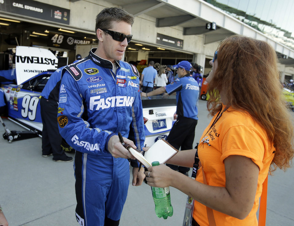 Photo - Driver Carl Edwards signs an autograph for a fan before practice for the Brickyard 400 Sprint Cup series auto race at the Indianapolis Motor Speedway in Indianapolis, Friday, July 25, 2014. (AP Photo/Darron Cummings)