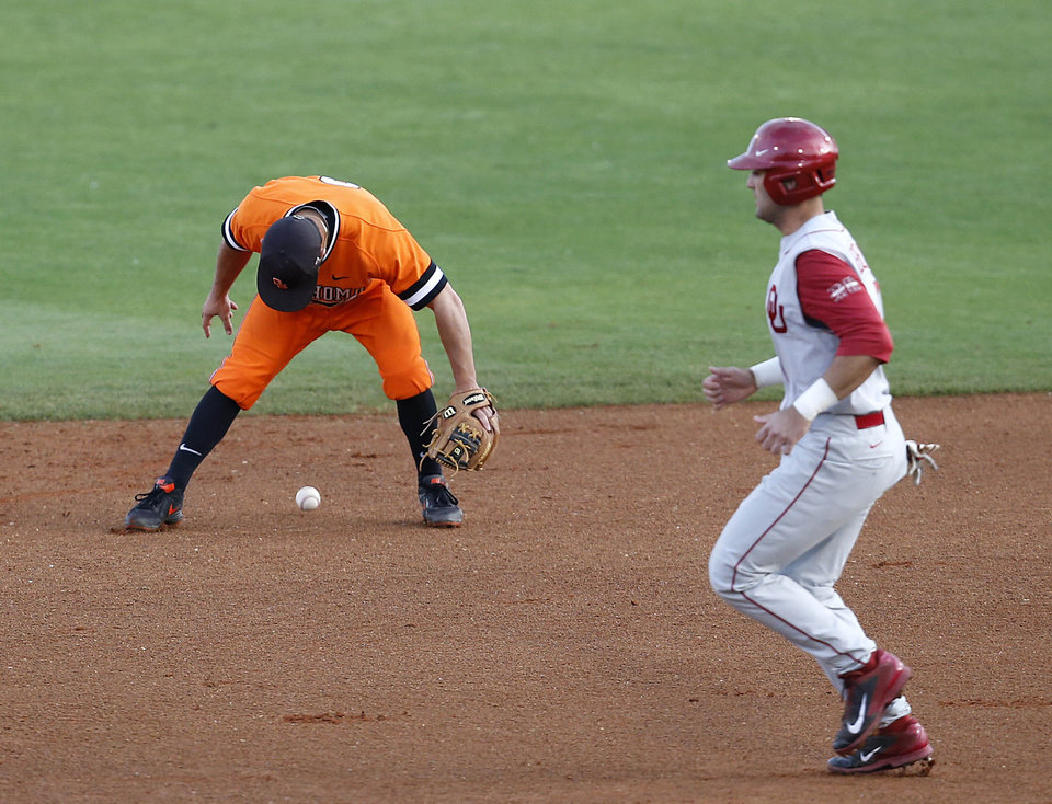Photo - Oklahoma State's Tim Arakawa, left, bobbles the ball as Oklahoma's Anthony Hermelyn heads for second base during an NCAA college baseball game in Tulsa, Okla., on Saturday, May 17, 2014. (AP Photo/Tulsa World, Matt Barnard)