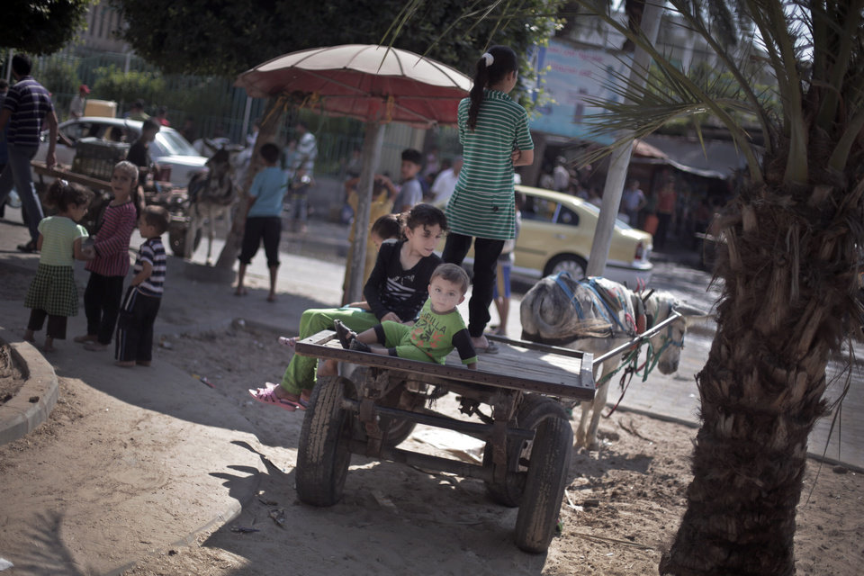 Photo - Palestinian children sit on a donkey cart waiting to fill a plastic container with drinking water at a public tap in the town of Jabaliya in the northern Gaza Strip, Sunday, July 27, 2014. Israel resumed its Gaza offensive on Sunday, calling off a unilateral extension of a humanitarian cease-fire after Palestinian militants fired several rockets at southern Israel. (AP Photo/Khalil Hamra)