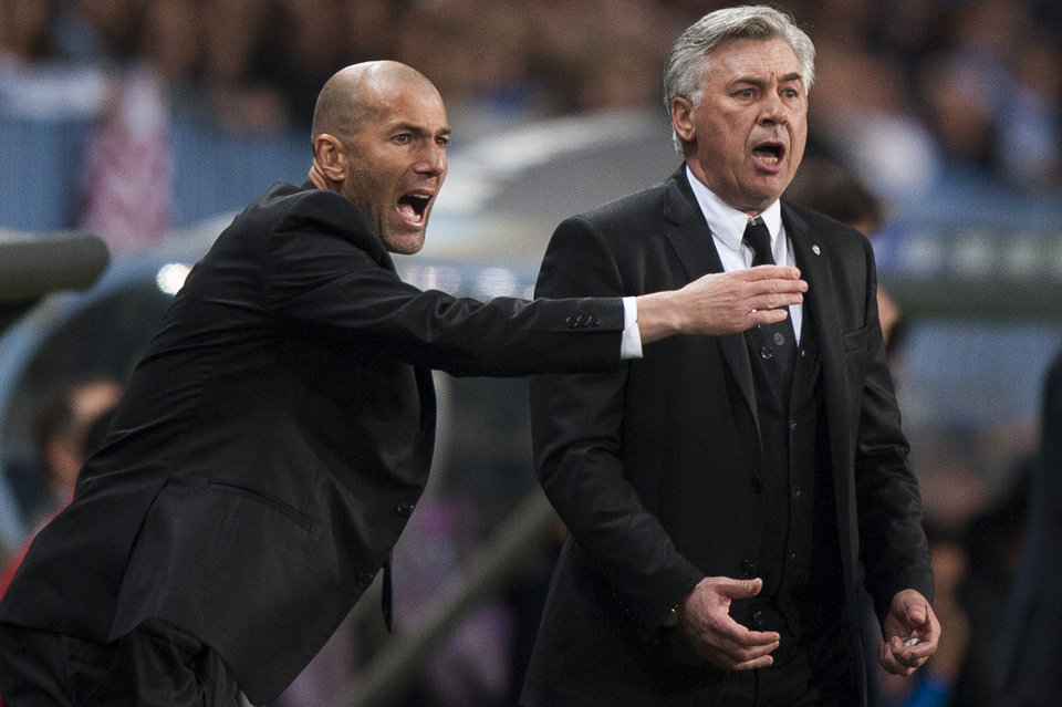 Photo - Real Madrid's assistant coach Zinedine Zidane from France, left, and coach Carlo Ancelotti from Italy, right, gesture during a Spanish La Liga soccer match at La Rosaleda stadium in Malaga, Spain, Saturday March 15, 2014. (AP Photo/Daniel Tejedor)