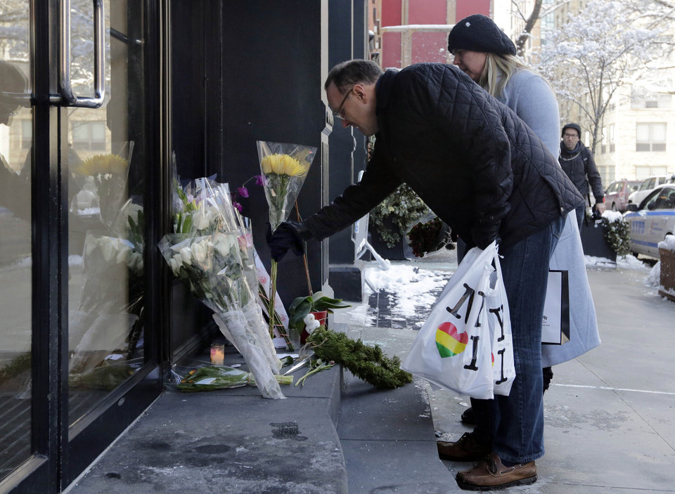 Photo - A couple adds to the flowers placed outside the apartment building of actor Phillip Seymour Hoffman, in New York,  Tuesday, Feb. 4, 2014. Autopsy results are expected soon in the death of actor Phillip Seymour Hoffman but police say it may take longer to determine if the heroin found in his apartment contains additives designed intensify the high. (AP Photo/Richard Drew)