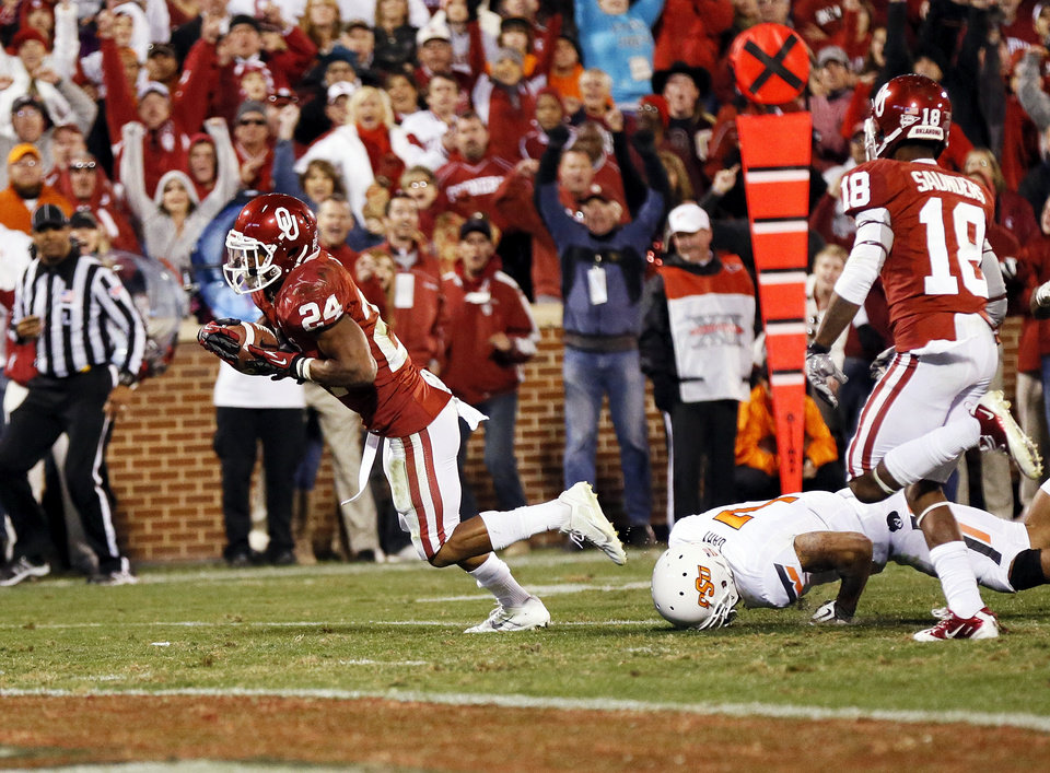 Oklahoma's Brennan Clay (24) gets past Oklahoma State's Shamiel Gary (7) on the game-winning touchdown run as Oklahoma's Jalen Saunders (18) looks on in overtime during the Bedlam college football game between the University of Oklahoma Sooners (OU) and the Oklahoma State University Cowboys (OSU) at Gaylord Family-Oklahoma Memorial Stadium in Norman, Okla., Saturday, Nov. 24, 2012. OU won, 51-48 in overtime. Photo by Nate Billings , The Oklahoman