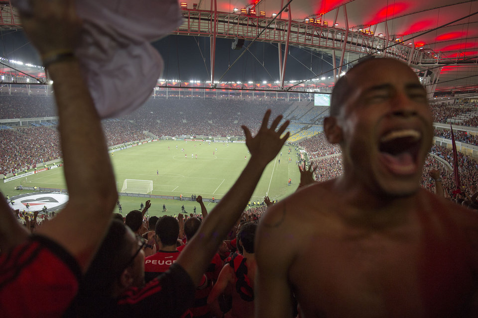 Photo - In this April 9, 2014 photo, a fan of Brazil's Flamengo soccer team celebrates his team's goal during a Copa Libertadores match in Maracana stadium in Rio de Janeiro, Brazil. Soccer's big moment happens in June as the best players on the planet meet in Brazil for the World Cup. Brazil is a five-time champion of the World Cup and is seeking a record sixth World Cup title, Brazil has won 13 of its last 14 games. (AP Photo/Leo Correa)