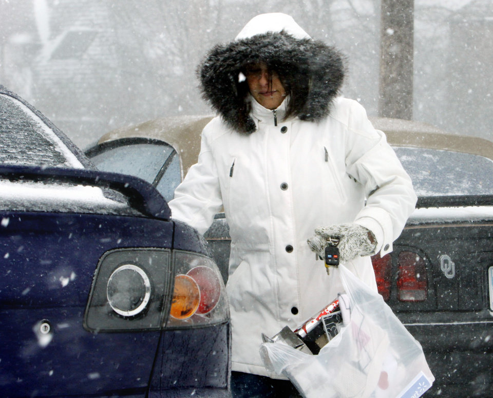 Photo - BLIZZARD / CHRISTMAS EVE / ICE / COLD / WINTER WEATHER / WINTER STORM / SHOP / SHOPPER / SNOWSTORM / SNOW: Michelle McHale of Midwest City walks to her car after shopping at Sooner Mall on Thursday, Dec. 24, 2009, in Norman, Okla.   Photo by Steve Sisney, The Oklahoman ORG XMIT: KOD
