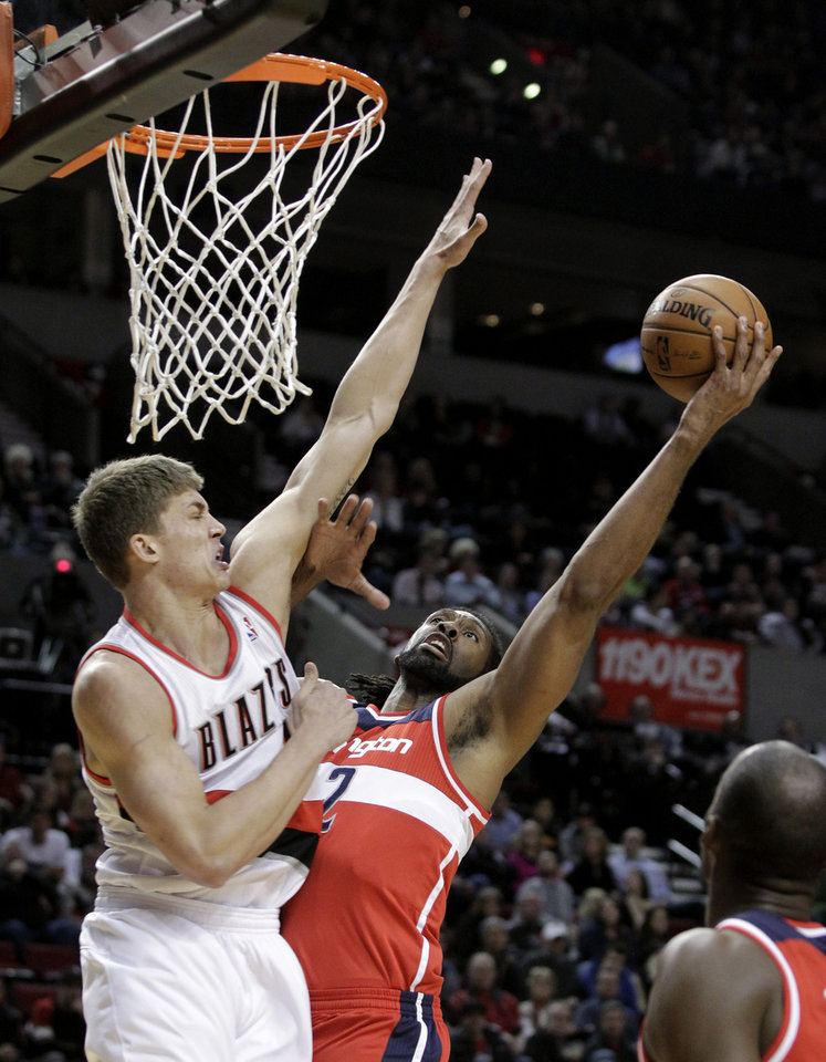 Photo - Washington Wizards guard John Wall, right, shoots against Portland Trail Blazers center Meyers Leonard during the first quarter of an NBA basketball game in Portland, Ore., Monday, Jan. 21, 2013. (AP Photo/Don Ryan)